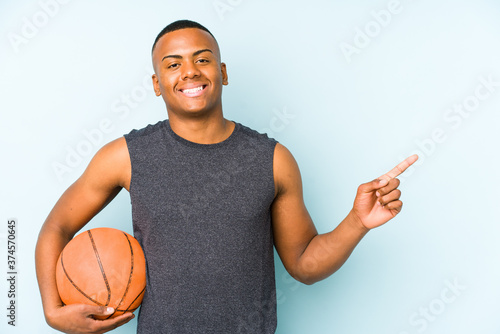 Fotografie, Obraz Young colombian man playing basketball isolated smiling and pointing aside, showing something at blank space