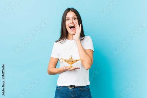 Obraz na plátně Young caucasian woman holding a magic lamp shouting excited to front