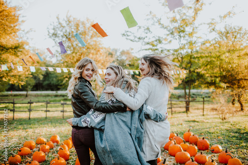 three teenage girls dance and laugh among mountain of pumpkins at the fall fair Wallpaper Mural
