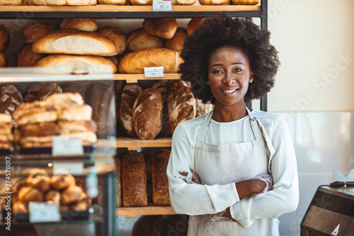 Obraz Portrait of positive African American young woman working in own Bakery shop, looking at camera with toothy smile. Pretty baker smiling at camera. Small Bakery shop owner standing in front of store - fototapety do salonu