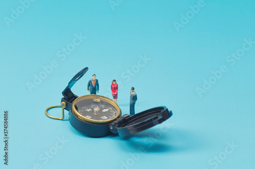 Foto Miniature businessman and compass on blue background