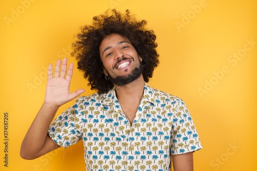 Young man with afro hair over wearing hawaiian shirt standing over yellow background Waiving saying hello happy and smiling, friendly welcome gesture Poster Mural XXL