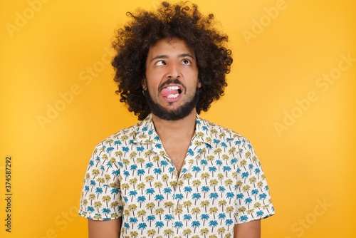 Fotografie, Obraz Young man with afro hair over wearing hawaiian shirt standing over yellow background showing grimace face crossing her eyes and showing tongue