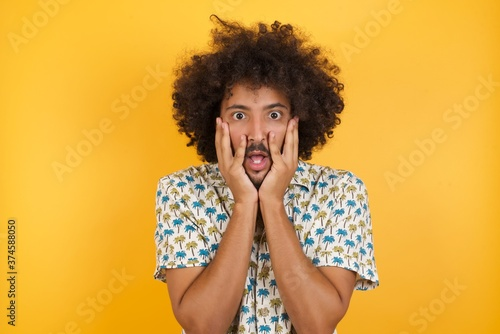 Fototapeta Stupefied Young man with afro hair wearing hawaiian shirt standing over yellow w