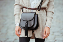 Fashionable Young Woman In Black Jeans, Beige Cardigan And Black Handbag . Street Style