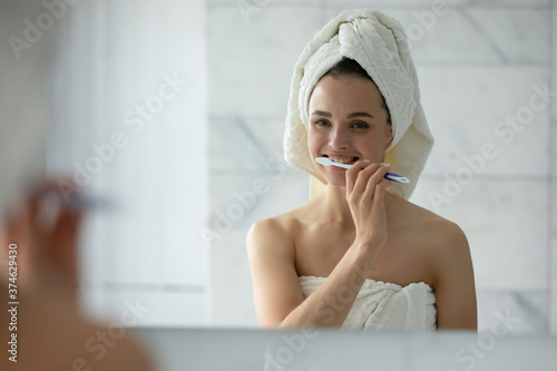 Stampa su Tela Close up head shot young woman with white bath towel on head cleaning teeth, usi