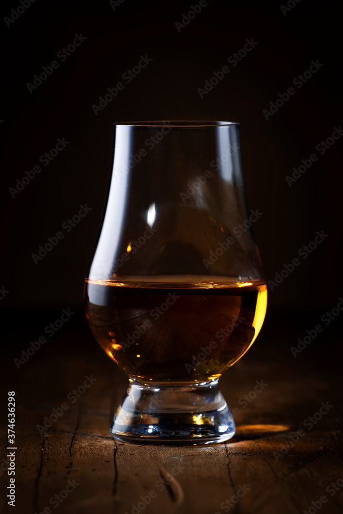 Fototapeta Scotch Whiskey without ice in glass, rustic wood background, copy space