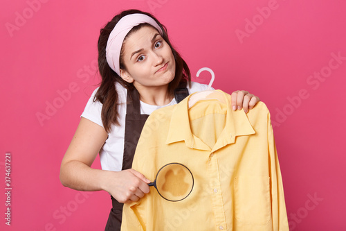 Sad female wears white t shirt, brown apron and hair band, holds yellow blouse and magnifier in front of large, looks at camera with puzzled expression,doe not know how to remove impurity Poster Mural XXL