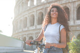 Fototapeta Londyn - Woman riding e-scooter while visiting the Colosseum in Italy