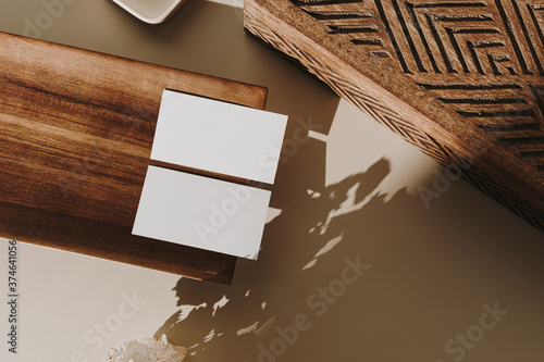 Fototapeta Blank paper sheet cards with mockup copy space, wooden tray, casket and dry flowers with sunlight shadow on beige background