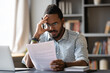 African American man wearing glasses dissatisfied by bad news received in letter, holding document, sitting at work desk, unexpected debt, bank or job dismissal notification, eviction notice