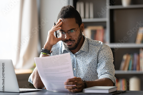 African American man wearing glasses dissatisfied by bad news received in letter Fototapeta