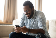 Smiling African American Man Using Phone, Sitting On Couch, Happy Young Male Holding Smartphone, Looking At Screen, Chatting In Social Network With Friends, Having Fun With Mobile Device At Home