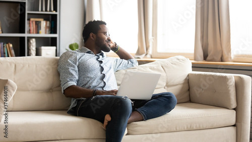 Smiling dreamy African American man sitting on couch with laptop, dreaming about Canvas