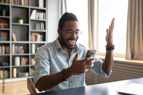Foto Happy surprised African American man excited by good news, using phone, positive