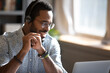 Smiling African American man wearing headphones speaking close up, using laptop, looking at screen, teacher holding online lesson, friendly call center customer service operator consulting client