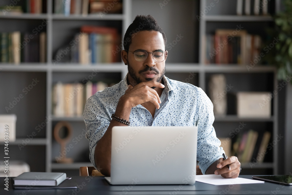 Fototapeta Thoughtful African American businessman looking at laptop screen, touching chin, pondering project plan or strategy, creative ideas, freelancer working online, sitting at desk in modern cabinet
