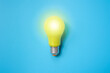 Bright yellow light bulb isolated on light blue background ,new idea ,innovation and creativity concept