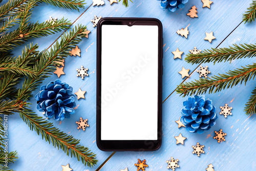 Obraz Phone on the table at Christmas with Christmas trees. - fototapety do salonu