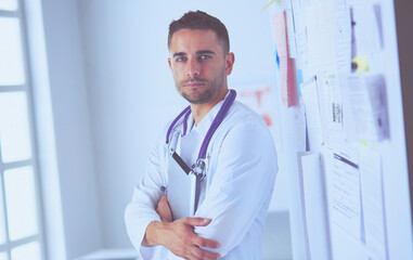 Young and confident male doctor portrait standing in medical office.