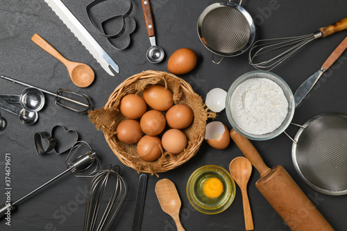 Carta da parati Fresh eggs in basket and Kitchen utensils for pastries on black table