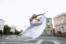 Girl Dancer In White Dress Jumps In Town