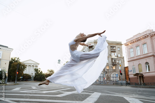 Girl dancer in white dress jumps in town Poster Mural XXL