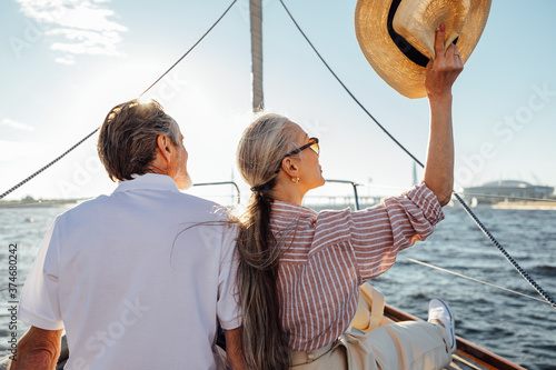 Fotografie, Obraz Back view of relaxed mature couple sitting on yacht