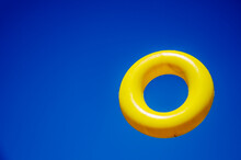 Yellow Toy Ring Against The Sky. Zero Hanging In The Air. Children's Toy Close-up.Yellow Bagel On A Bright Blue Background. Toy Ring In The Air. Bagel Close Up