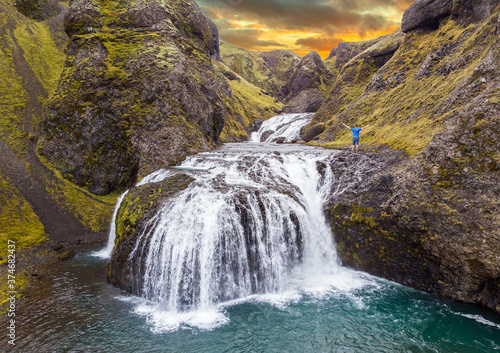 View from flying drone of Stjornarfoss waterfall. with person Impressive summer sunrise in Iceland, Europe. Beauty of nature concept background. Travel to Iceland..