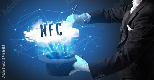 Magician is showing magic trick with NFC abbreviation, modern tech concept Wallpaper Mural