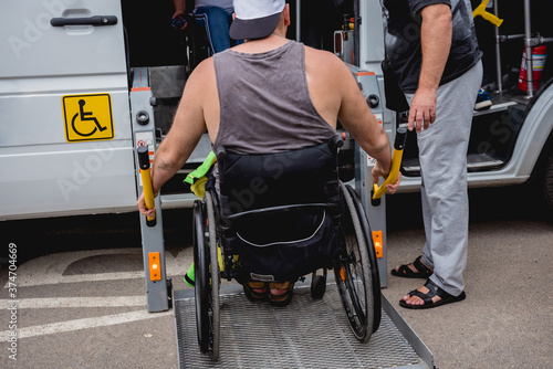 Fototapeta Disabled man on wheelchair using accessible vehicle with lift mechanism