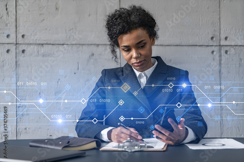 Fotografía Businesswoman taking notes and tech drawing hologram