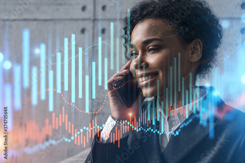 Fotografiet Businesswoman speaks phone and stock market financial chart hologram