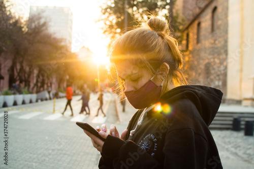 joven mujer con mascara usando celular en exterior Billede på lærred