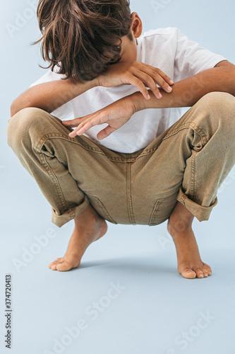 Emotionless indian asian kid sitting low, knees up, covering face with his arm Billede på lærred