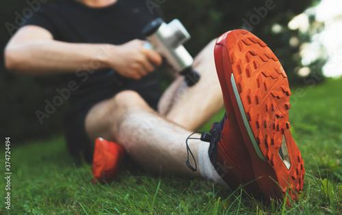 Fotografie, Obraz Man massaging leg with massage percussion device after workout.