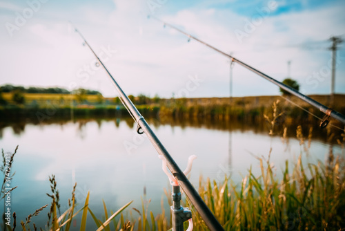 Photo Fisherman`s fishing rod with inertia-free coil in summer on shore of pond