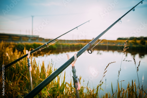 Vászonkép Fisherman`s fishing rod with inertia-free coil in summer on shore of pond
