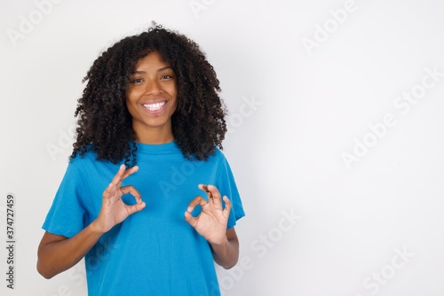 Fotografie, Obraz Young african woman with curly hair wearing casual blue shirt over white background showing both hands with fingers in OK sign