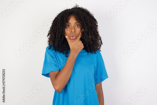 Young african woman with curly hair wearing casual blue shirt over white backgro Canvas Print