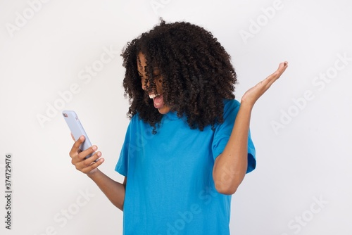 Photo Angry Young african woman with curly hair wearing casual blue shirt screaming on the phone, having an argument with an employee
