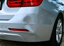 Backside Of Car Has Dented Rear Bumper Damaged After Accident In The Parking Lot.