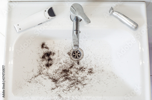 Obraz na plátně Shaved hairs in the washbasin with razor and trimmer
