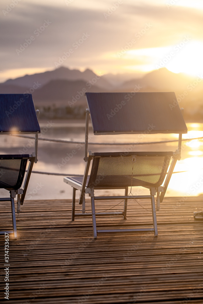 Fototapeta Two empty chairs on a wooden pier at sunset