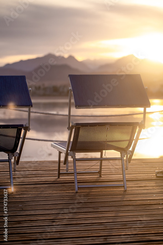 Obraz Two empty chairs on a wooden pier at sunset - fototapety do salonu