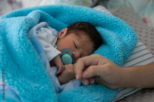 Female hand holding her newborn baby's hand Fototapeta