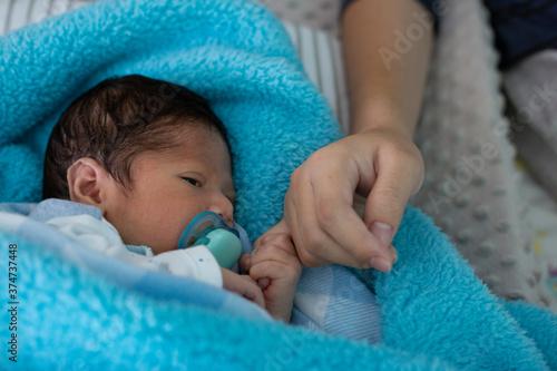 Obraz na płótnie Female hand holding her newborn baby's hand