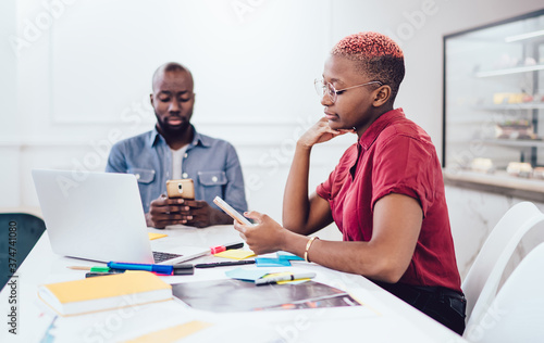 Fototapeta Black colleagues surfing Internet on smartphones at workplace