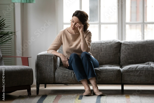 Fotografia Full length unhappy stressed 50s old woman feeling insecure alone at home, thinking pondering of hard decision
